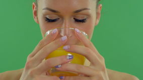 Young beautiful woman drinking orange juice and enjoy and looking at the camera on the green screen with alpha channel 24. stock footage