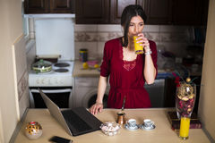 Young beautiful woman drinking orange juice in the kitchen Royalty Free Stock Images