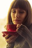Young Beautiful Woman Drinking Tea with Steam. Warm color toned Royalty Free Stock Images