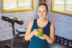 Young beautiful woman drinking vegetable smoothie after fitness at home and smile . Fitness and healthy lifestyle royalty free stock photos