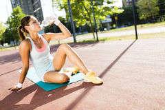Young beautiful woman drinking water after exercise in a city tr Stock Image