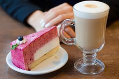 Young beautiful woman drinks coffee latte with foam on the table cake Stock Photos