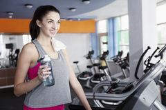 Young beautiful woman drinks water on the treadmill in the gym stock image