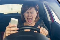 Beautiful woman  driving car while texting using mobile phone distracted Royalty Free Stock Image