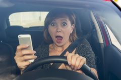 Beautiful woman  driving car while texting using mobile phone distracted Stock Photos