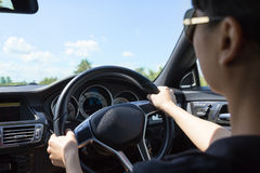 Young beautiful woman driving a luxury car on road. Royalty Free Stock Photography