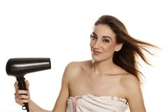 Woman drying her hair. Young beautiful woman drying her hair with a blow dryer on a white background royalty free stock photography