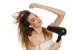 Woman drying her hair. Young beautiful woman drying her hair with a blow dryer on a white background stock photos