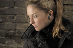 Young beautiful woman with earbud. Royalty Free Stock Photo