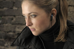 Young beautiful woman with earbud. Royalty Free Stock Photography