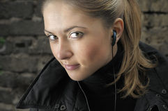 Young beautiful woman with earbud. Royalty Free Stock Images