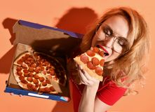 Young beautiful woman eat pepperoni pizza slice and hold whole pizza in box on orange Royalty Free Stock Photography