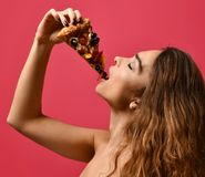 Young beautiful woman eat slice of pepperoni pizza smiling on dark red. Background royalty free stock photos