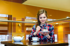 Young beautiful woman eating cake in cafe Stock Image