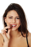 Young beautiful woman eating chocolate bar Stock Image