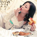 Young beautiful woman eating croissant with jam Stock Photos