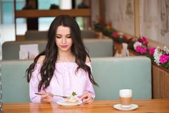 Young beautiful woman eating a dessert in a cafe. royalty free stock photo