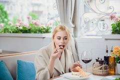 Young beautiful woman eating a dessert. At the restautant. woman gets pleasure from eating Stock Photos