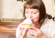Young beautiful woman eating a dessert. Sweet life with cake royalty free stock images