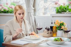 Young beautiful woman eating a dessert royalty free stock photography