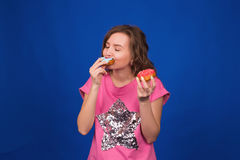Young beautiful woman eating doughnuts on blue background. Unhealthy diet, junk food and food addiction concept Royalty Free Stock Photos