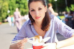 Young beautiful woman eating fast food noodles in st Stock Photography