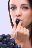 Young beautiful woman eating grapes Stock Image