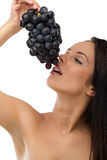 Young beautiful woman eating grapes Royalty Free Stock Photography