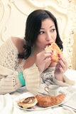 Young beautiful woman eating her croissant. Portrait of a young beautiful woman eating her croissant with strawberry jam in a vintage bedroom. Indoor shot Stock Image
