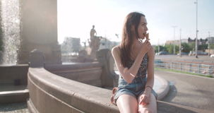 Young beautiful woman eating ice cream during sunny day, outdoors. stock video footage