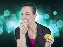 Woman and lemon. Young beautiful woman eating sour lemon Royalty Free Stock Photos