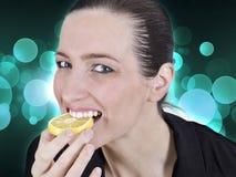 Woman and lemon. Young beautiful woman eating sour lemon stock image