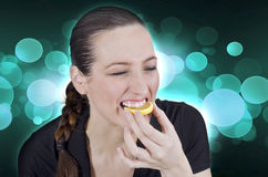 Woman and lemon. Young beautiful woman eating sour lemon Royalty Free Stock Photography
