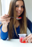 Young beautiful woman eating yogurt at home. Royalty Free Stock Photography