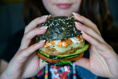 Young beautiful woman eats burger in restaurant royalty free stock images