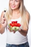Young beautiful woman eats vegetable salad. Healthy eating. To be in shape. Royalty Free Stock Image