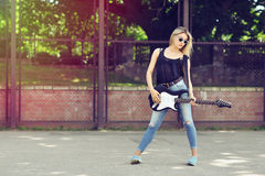 Young beautiful woman with electric guitar wearing sunglasses Royalty Free Stock Photography