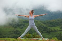 Young beautiful woman is engaged in hatha yoga in the morning misty mountains Royalty Free Stock Photography