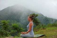 Young beautiful woman is engaged in hatha yoga in the morning misty mountains Stock Photo