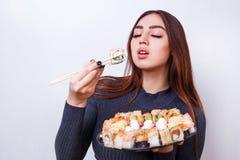 Young beautiful woman enjoy eating sushi, studio shoot on white stock images