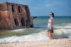 Young beautiful woman enjoying beach vacation. In background part of the old demolished forts in Liepaja, Latvia on the Baltic sea coast Royalty Free Stock Image