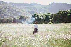 Young beautiful woman enjoying chamomile field among mountains Royalty Free Stock Photo