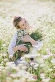 Young beautiful woman enjoying chamomile field among mountains Stock Images