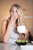 Young beautiful woman enjoying healthy breakfast in the kitchen Stock Images