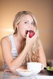 Young beautiful woman enjoying healthy breakfast in the kitchen Royalty Free Stock Photo
