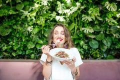 Woman eating salad at the vegetarian restaurant