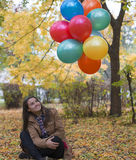 Young and beautiful woman enjoying her balloons. Colored ballons and youg woman in autumn season royalty free stock image