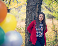 Young and beautiful woman enjoying her balloons. In the forest Royalty Free Stock Photos