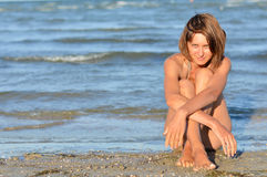 Young beautiful woman enjoying sea view on sandy beach. Summer outdoors background Royalty Free Stock Image