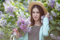 Spring portrait of a beautiful woman outdoors in the park, among the bushes blooming lilac. Young beautiful woman enjoying the smell of blooming lilac on a sunny royalty free stock images